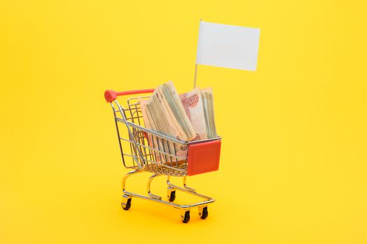 In the grocery cart lies a bundle of five thousandth bills and a white flag is set