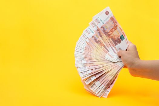 Hand holds a fan from a pack of five thousandth Russian bills on a yellow background