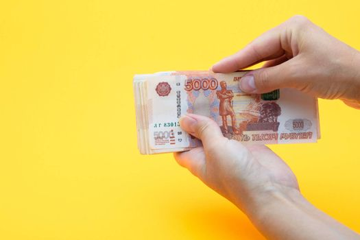 Two hands holding a crustacean of five thousandth Russian rubles on a yellow background
