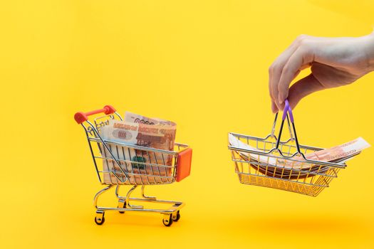 Five thousandth bills are in the grocery cart, a hand holds a grocery basket with bills