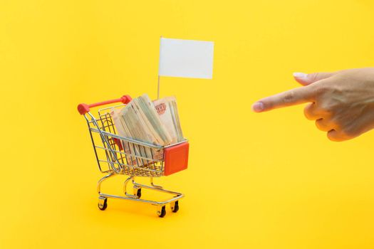 Hand points to a grocery cart with a bundle of notes and a white flag for inscription