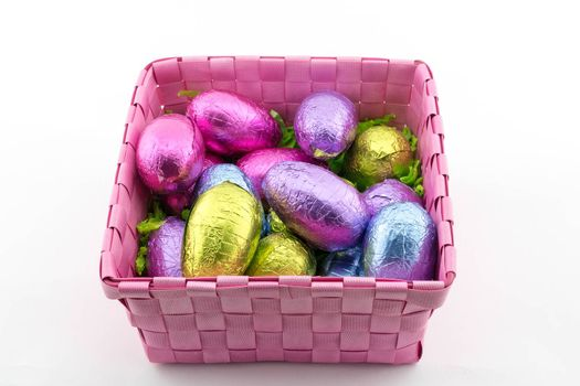 Multi-coloured Easter eggs in a pink basket