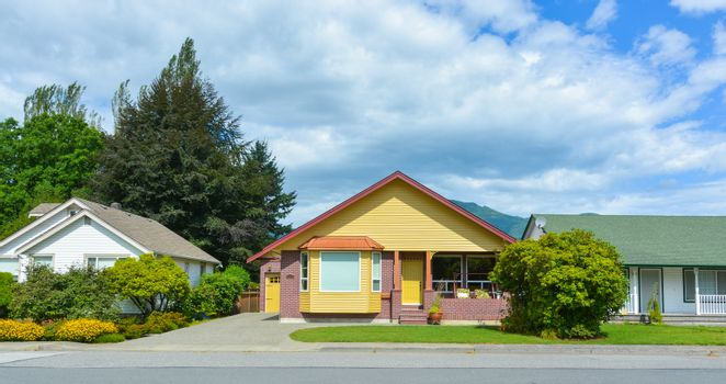 Yellow residential house with accurate lawn and concrete driveway to the garage