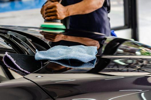 Man hands holding the work tool polish the car. Car detailing.Select focus on microfiber cloths.