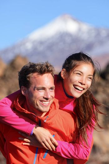 Happy couple piggyback in active lifestyle having fun on hike. Fresh young joyful interracial couple. Asian woman hiker and Caucasian man in outdoor activity on Teide, Tenerife, Canary Islands, Spain