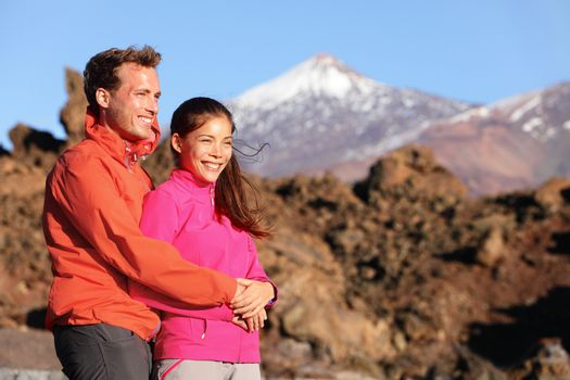 Happy couple in in love in active lifestyle hiking looking at view on hike. Romantic young interracial couple. Asian woman hiker and Caucasian man outdoors on Teide, Tenerife, Canary Islands, Spain