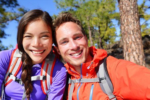 Selfie couple taking self-portrait hiking candid