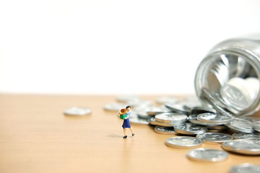 monthly expenditure - Women spend savings to shop. Miniature people figure conceptual photography.