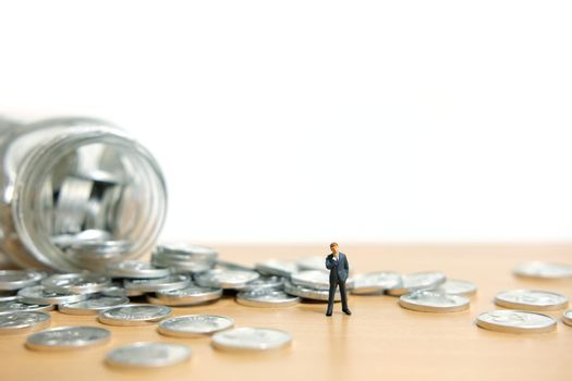 Businessmen standing watching scattered money from a bottle. Miniature people figure conceptual photography.