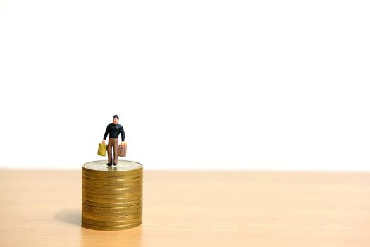 A man standing above coin stack to protect money. Miniature people figure conceptual photography.