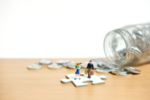monthly expenditure, women and men standing above white puzzle jigsaw piece spending money. Miniature people figure conceptual photography.