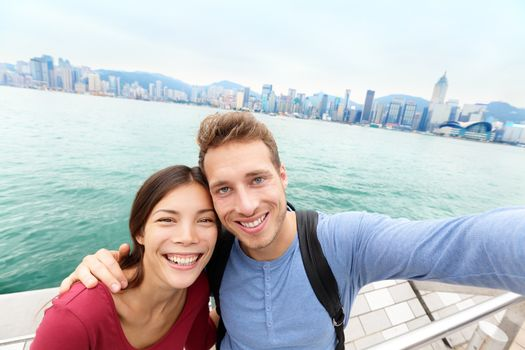 Selfie - Tourists couple taking selfportrait picture photo in Hong Kong enjoying sightseeing on Tsim Sha Tsui Promenade and Avenue of Stars in Victoria Harbour, Kowloon, Hong Kong. Travel concept.