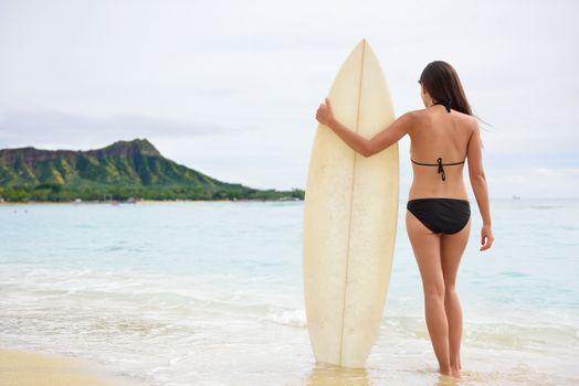 Surfer woman going surfing standing with surfboard on Waikiki Beach, Oahu, Hawaii. Female bikini girl walking with surfboard living healthy active lifestyle on Hawaiian beach. Asian Caucasian model.