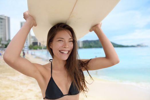 Portrait of surfer woman on Waikiki Beach, Oahu, Hawaii. Female bikini girl walking with surfboard smiling happy having fun living healthy active lifestyle on Hawaiian beach. Asian Caucasian model.