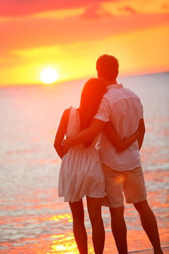 Honeymoon couple romantic in love at beach sunset. Newlywed happy young couple hugging enjoying ocean sunset during travel holidays vacation getaway. Interracial couple, Asian woman, Caucasian man.