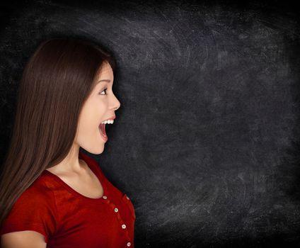 Excited happy woman by blackboard / chalkboard