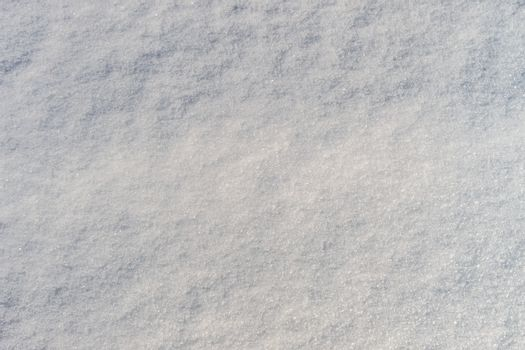 Snow texture at sunny winter day. Abstract background with shadows and highlights.