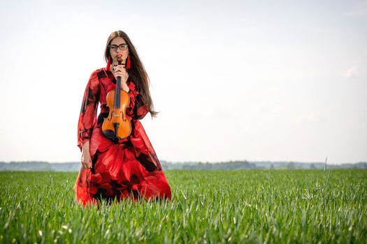 Young woman in red dress with violin in green meadow.