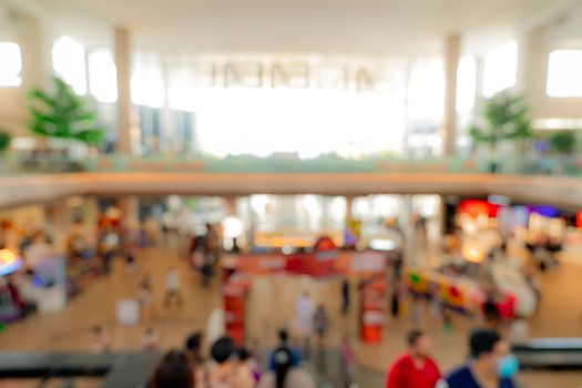 Blur crowded people inside shopping mall. Defocus retail shop in