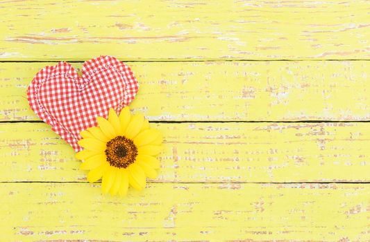 Red heart with yellow blossom on wooden background with copy space