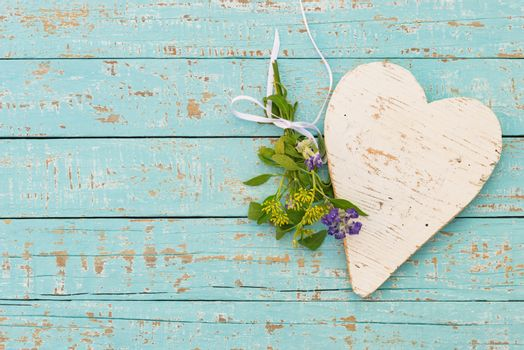 Turquoise background with white wooden heart and bunch of flowers with copy space