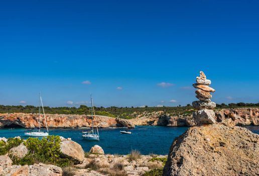 Idyllic bay with boats and stone stack at the coast of Mallorca, Spain Balearic Islands
