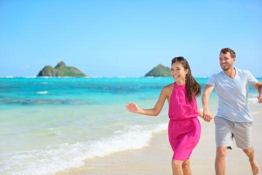 Beach couple happy running having fun on Hawaii. Romantic couple cheerful and full of happiness on travel vacation on Lanikai beach, Oahu, Hawaii, USA with Mokulua Islands. Asian woman, Caucasian man