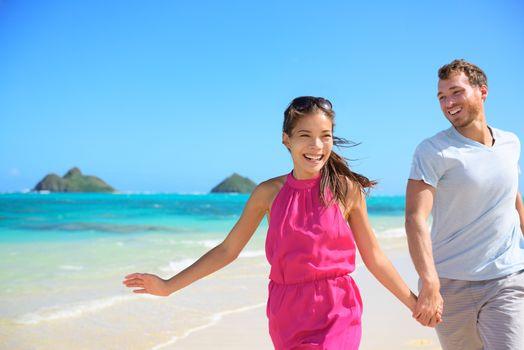 Happy couple on beach running having fun on Hawaii. Romantic couple joyful and full of happiness on travel vacation on Lanikai beach, Oahu, Hawaii, USA with Mokulua Islands. Asian woman, Caucasian man