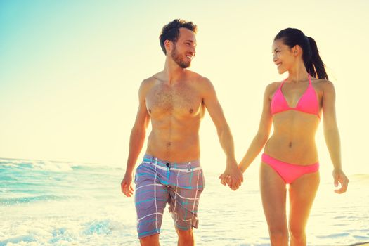 Honeymoon couple romantic in love holding hands at beach sunset. Newlywed happy young couple enjoying ocean sunset during travel holidays vacation getaway. Interracial couple.