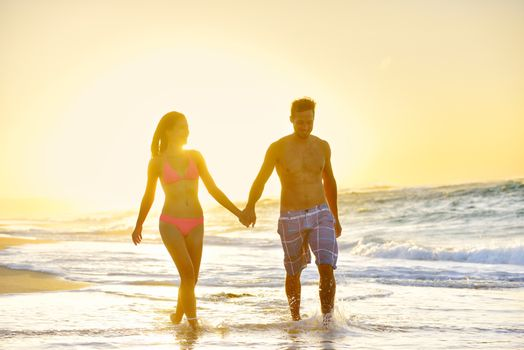 Romantic honeymoon couple in love holding hands walking on beautiful sunset at beach in waterfront. Lovers or newlywed married young couple by the sea enjoying vacation travel holiday. Oahu Hawaii USA