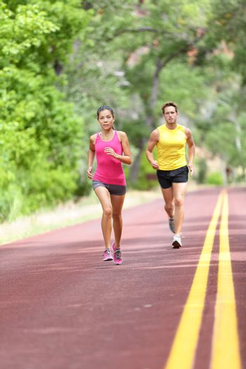 People running on road. Sport and fitness runners woman and man training for marathon run doing high intensity interval training sprint workout outdoors. Athletes sports models fit and healthy.