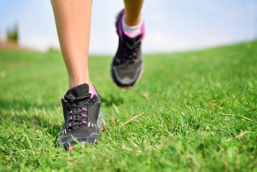 Runner athlete feet running on grass fitness woman