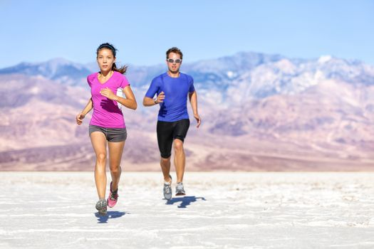 Runners trail running on dry desert landscape. Couple of fit athletes sprinting in compression activewear wearing sports clothing sweating in hot weather. Full length people in dramatic nature.