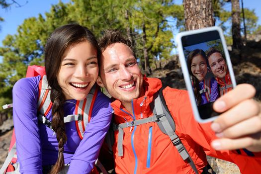 Happy friends hikers taking selfie on hiking trip. Couple posing for self-portrait picture on smartphone during summer holidays vacation travel camping and backpacking. Young multiracial couple.