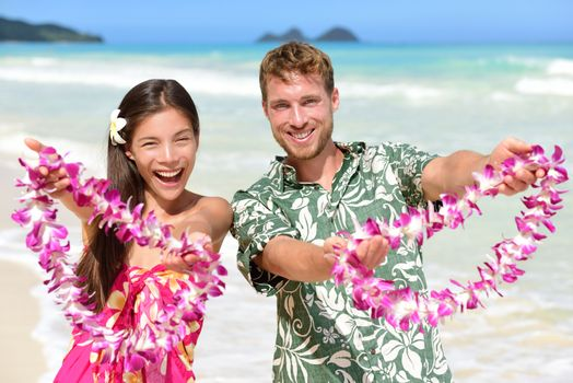 Welcome to Hawaii - Hawaiian people showing giving leis flower necklaces as welcoming gesture for tourism. Travel holidays concept. Asian woman and Caucasian man on white sand beach in Aloha clothing.
