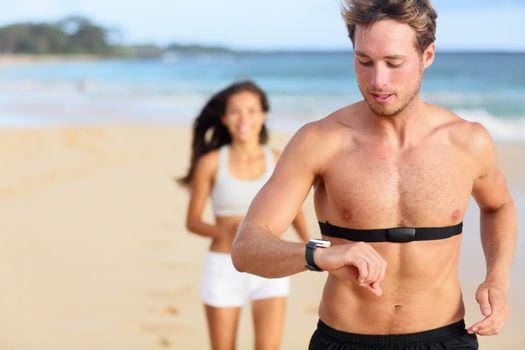 Running young man jogging on beach using heart rate monitor. Handsome shirtless male runner working out outside by the ocean wearing heart rate monitor. Closeup portrait of fit fitness athlete model.