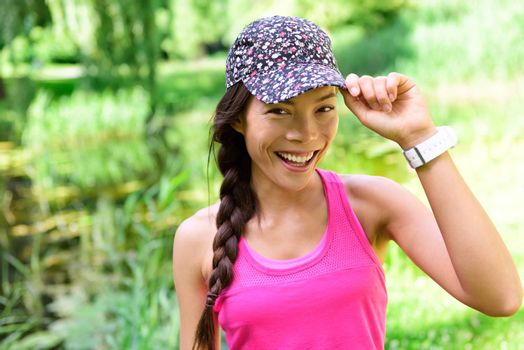 Portrait of woman runner wearing running cap. Female athlete smiling happy at camera after jogging in city park wearing floral headwear hat.