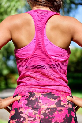 Woman runner in mesh tank top activewear and floral leggings. Female runner after workout.