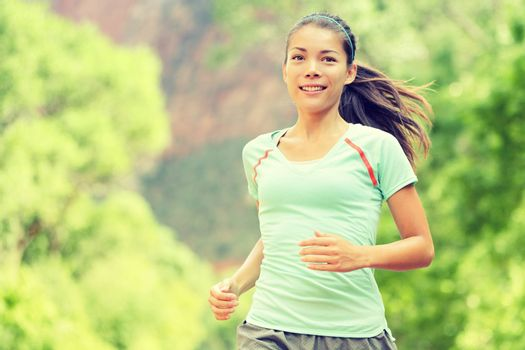 Young woman jogging while smiling. Beautiful mixed race Asian / Caucasian female is in sports clothing. Attractive lady is in park.