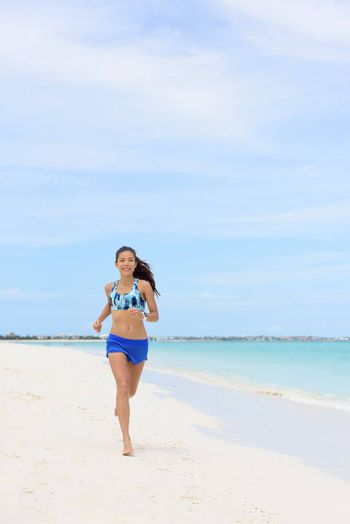 Beach running Asian woman doing morning cardio workout on white sand and turquoise ocean water training cardio for weight loss. Copyspace on blue sky.