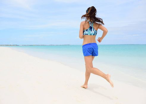Runner training cardio running on beach. Back view of woman jogging barefoot in tropical destination barefoot in activewear blue sports bra and active shorts living a healthy life.