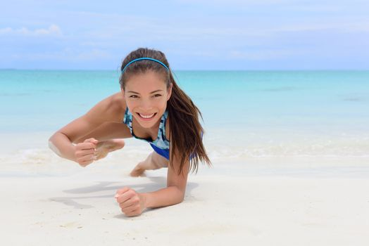 Core body workout - fitness woman planking doing forearm one arm spiderman knee to elbow crunch plank. Young Asian Chinese adult girl on beach strength training as part of a healthy lifestyle.