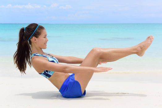 Fitness woman on white sand beach and turquoise ocean background exercising abs with sit-ups workout. Young female athlete doing ab toning exercises with v-up crunches as basic core body poses.