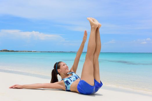 Abs exercise fitness woman - toe touch crunchesFitness woman training abs with toe touch crunches. Young adult Asian girl doing abdominal exercises