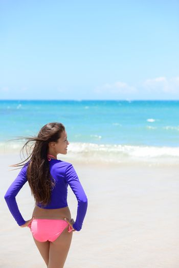 Woman relaxing on beach looking at the waves in sun protective swimwear t-shirt / rashguard to protect skin against rashes and uv rays during swimming or surfing.