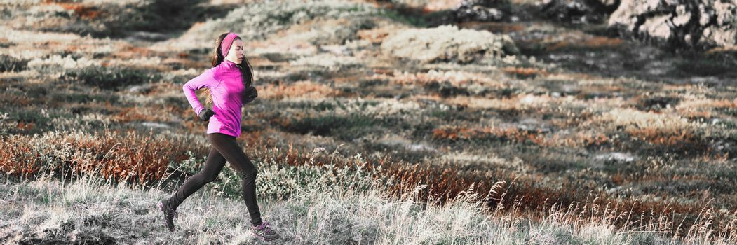 Running woman in winter trail mountain banner background. Runner athlete training cardio in cold weather outdoors. Asian girl wearing warm leggings and pink clothing.