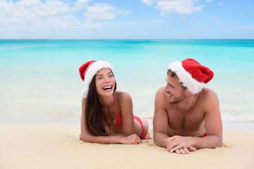 Christmas couple relaxing on beach winter vacation. Happy young adults friends or in love laughing on white sand in tropical travel destination for their new year holiday.