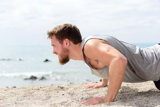 Fitness man doing push-up exercise on beach. Portrait of fit guy working out his arm muscles and body core with pushup exercises on sand beach.