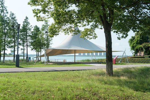 A sailboat tent by the lake, public park scenery. Photo in the public park.