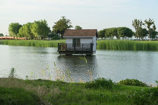 The cottage over the lake in the public park. Photo in Suzhou, China.